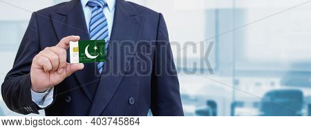 Cropped Image Of Businessman Holding Plastic Credit Card With Printed Flag Of Pakistan. Background B