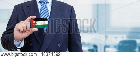 Cropped Image Of Businessman Holding Plastic Credit Card With Printed Flag Of Palestine. Background