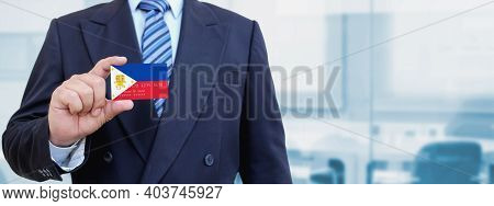 Cropped Image Of Businessman Holding Plastic Credit Card With Printed Flag Of Philippines. Backgroun