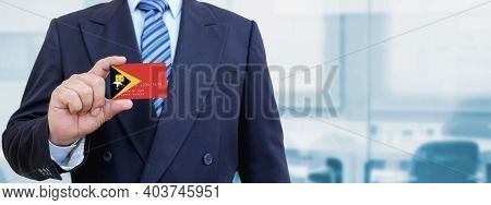 Cropped Image Of Businessman Holding Plastic Credit Card With Printed Flag Of East Timor. Background