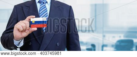 Cropped Image Of Businessman Holding Plastic Credit Card With Printed Flag Of Russia. Background Blu