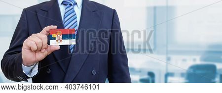 Cropped Image Of Businessman Holding Plastic Credit Card With Printed Flag Of Serbia. Background Blu