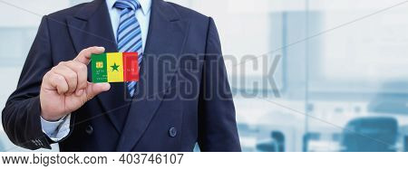 Cropped Image Of Businessman Holding Plastic Credit Card With Printed Flag Of Senegal. Background Bl
