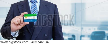 Cropped Image Of Businessman Holding Plastic Credit Card With Printed Flag Of Sierra Leone. Backgrou