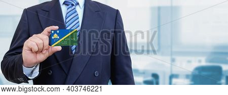 Cropped Image Of Businessman Holding Plastic Credit Card With Printed Flag Of Solomon Islands. Backg