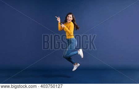 Happy Young Asian Woman In Colorful Yellow Color Casual Clothes Jumping And Presenting To Copy Space
