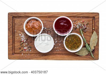 Different Types Of Sauces In Bowls On A Cutting Board. Restaurant Service Concept. Isolated.