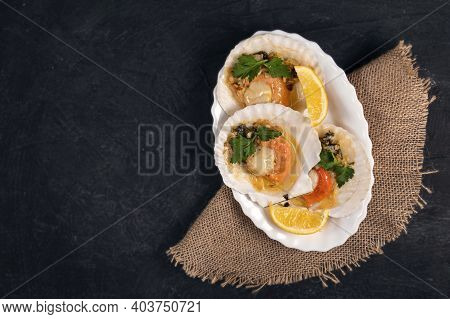 Baked Scallops With Caviar And Creamy Garlic Sauce In White Plate. Scallops With Lemon On Black Back