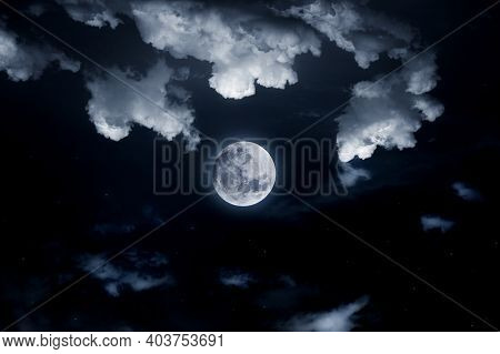 Moon in the night sky. Moon among the stars and clouds. Space satellite of the Earth in the solar system galaxy.