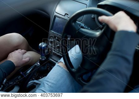 Man put his hand on a woman's knee in a car, harassment in the car. Sexual harassment concept