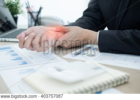 Businessman Grasping The Painful Wrist Caused By Prolonged Work On A Laptop Keyboard. Wrist Numbness