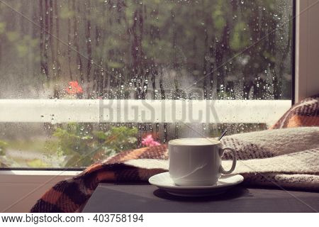 Hot Coffee In A Mug On The Table With A Blanket And Against The Window After The Rain. Warming Home