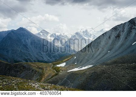 Trail Through Stony Hills To Beautiful Huge Glacier Mountains Under Gray Cloudy Sky. Awesome Dramati