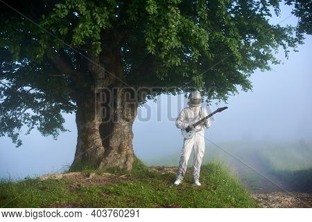 Space Traveler Playing On Guitar Near Large Tree. Astronaut Guitarist Wearing White Space Suit And H