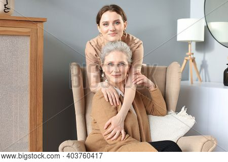 Elderly Middle Mother Sitting In A Chair And Her Daughter Are Hugging, Looking At Camera, Trusted Re