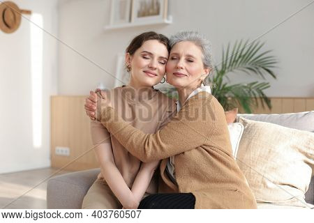 Cheerful Young Woman Is Embracing Her Middle Aged Mother With Closed Eyes Hugging, Touching Cheeks,