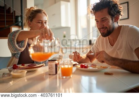 A happy young couple likes to have fresh orange juice for a breakfast on a beautiful sunny morning at home too. Relationship, love, together, breakfast