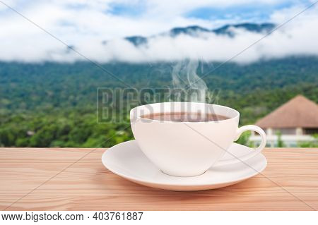 Tea Cup With Organic Tea Leaf On The Wooden Table And Tea Plantations. Warm Cup Of Tea. Space For Te