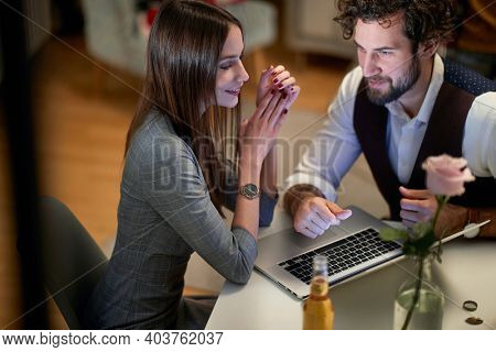 A young handsome business couple having a date in a relaxed atmosphere at an apartment. Business, date, relationship