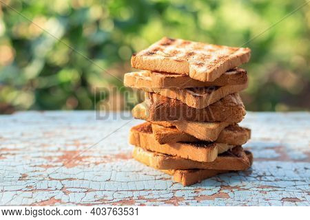 A Stack Of Delicious Crunchy Croutons Fried Over A Fire On The Background Of Nature. Bbq Toast For A