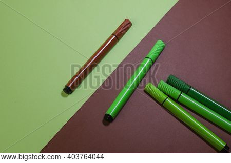Creative Two-color Composition With Green And Brown Felt-tip Pens. One Brown Felt-tip Pen Versus Fou