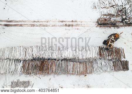 Loader Loads Logs Stacked In Piles Covered With Snow Top View