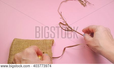 Florist Hands Prepare Dry Grass And Canvas Bag For Composition, On Pink Background, Diy Concept