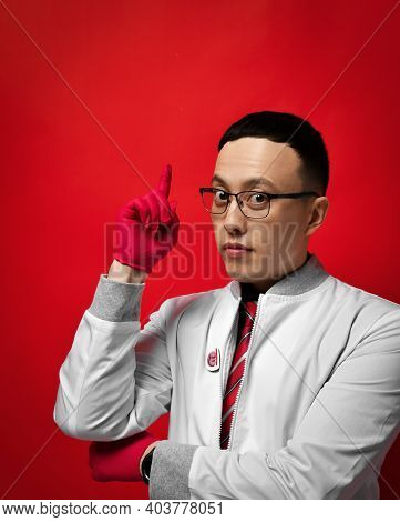 Portrait Of Young Man Doctor Urologist Or Proctologist In Medical Gown And Latex Gloves Holds Forefi