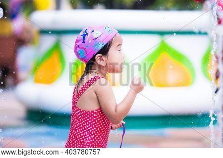 Selective Focus. Portrait Little Girl Was Agape The Fountain Pouring Out From The Ground In Front Of