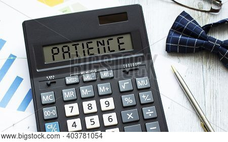 A Calculator Labeled Patience Lies On Financial Documents In The Office. Business Concept.