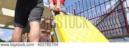 Man And Woman Carry Yellow Suitcase On Platform. Couple Arrive At Their Destination At Railway Stati