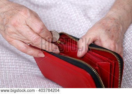 Elderly Woman Takes Out A Coin From Her Wallet, Wrinkled Female Hands Closeup. Concept Of Poverty, P