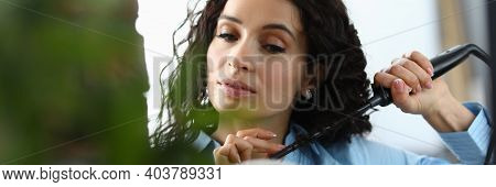 Beautiful Woman Look In Mirror And Wind Her Hair. Person Make Curl For Herself With Curling Iron.