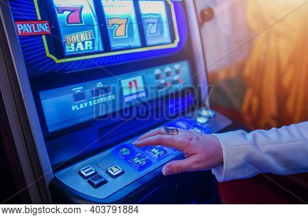 Caucasian Woman In Her 40s Playing Classic Slot Machine Game Inside One Of The Las Vegas Casino. Gam