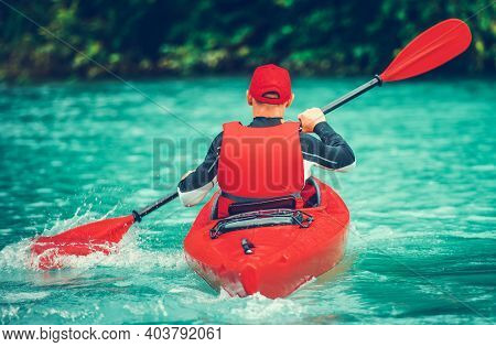 Caucasian Kayaker On The Scenic Glacial Lake Trip. Turquoise Water Color And Red Kayak. Kayaker Rear