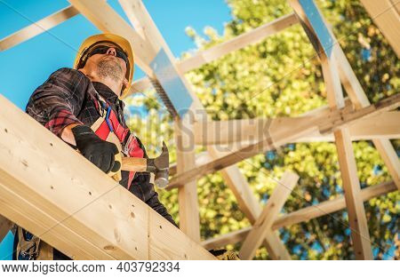 Caucasian Construction Worker In His 40s Between Wooden Roof Elements Of The House Skeleton Frame. C
