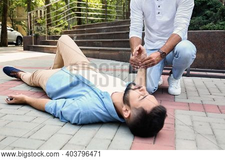 Passerby Checking Pulse Of Unconscious Young Man On City Street. First Aid