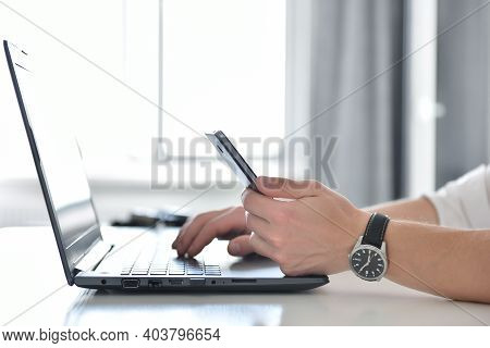 Trader Man Using Smart Phone And Typing On Laptop. Finance And Trade Concept. Close Up