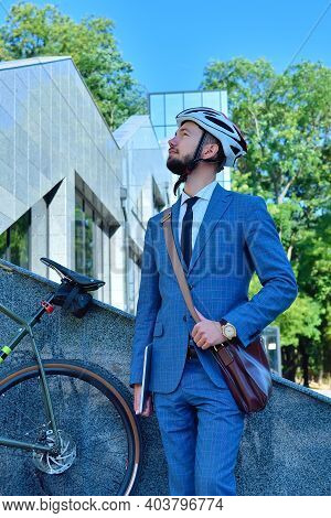 Bearded Businessman In Helmet With Bicycle Stands Near Business Center. Business And Urban Style Con