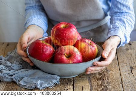 Apple Saved. Apples Washed In A Bowl In The Hands Of The Girl. A Plate With Red Apples On A Wooden T