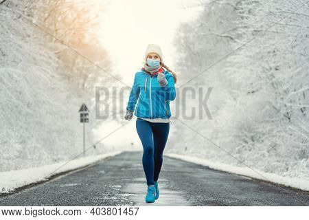 Woman running or jogging with face mask in the covid-19 winter during snowy landscape