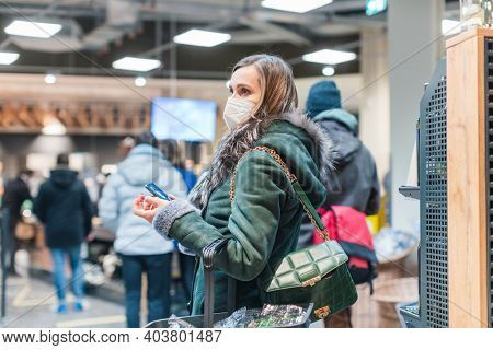 Woman standing in queue at cash desk in supermarket wearing mask keeping social distance