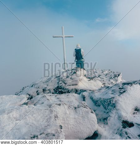 Woman standing near summit cross on a mountain summit