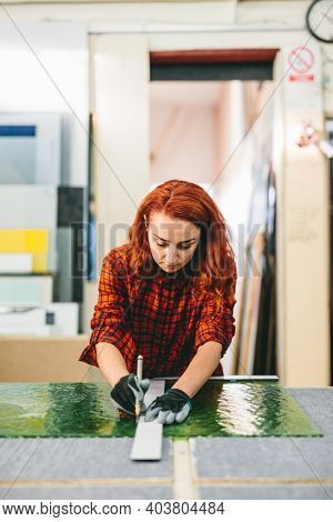 Glazier woman worker cutting glass in workshop. Industry and manufactory production