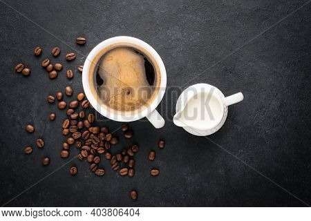 Cup Of Black Coffee And Coffee Creamer In A Jug On Black Concrete Background, Top View