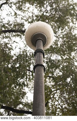 Long Lamppost With A Round Lamp Shade.