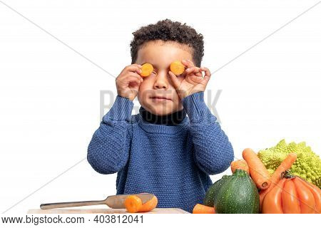 Close Up Portrait Of Cute Afro American Boy Holding Carrot Pieces In Front Of Eyes. Kid Next To Vege