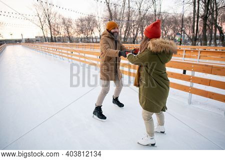 Young couple in warm clothing having fun on ice rink outdoors during winter vacation