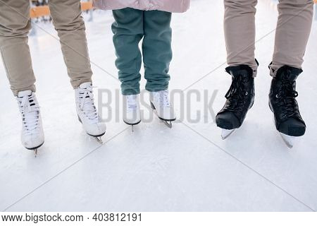 Close-up of family of three wearing skates standing on skating rink they going to skate
