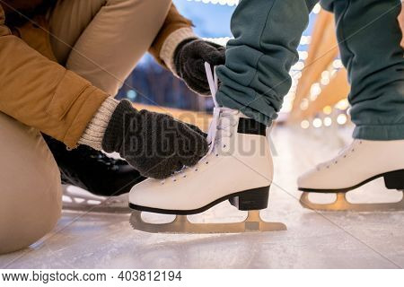 Close-up of man tying shoelace on skates of his girlfriend while they standing on skating rink